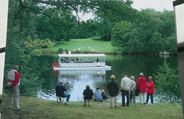 Vykortet visar E/S Vågspelet som glider fram på Bysjön - Den 26 augusti 2004 konserterade Överums Musikkår på musikbåten och publiken lyssnade längs stränderna. Foto Lena Källström